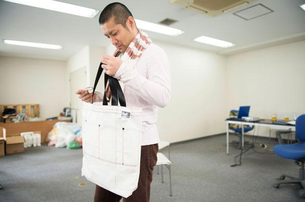 トートバッグを真剣に吟味する山崎亮さん