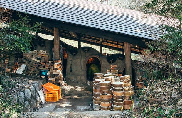焼きものの産地らしい登り窯のある風景。上には屋根がかかっている。手前に積んであるのは窯入れに使う「サヤ」という窯道具。