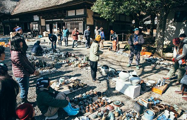 益子参考館の中庭に広げられた、窯出し作品の数々。参加者同士助け合い、和気あいあいと作業が進む。