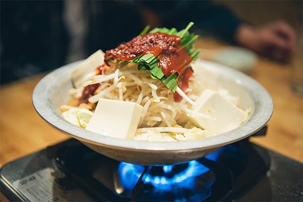 モツ鍋1人前850円(写真は1.5人前、ピリ辛タイプ)。5月下旬から8月はチリトリ鍋を使ってスープ抜きの赤焼きに。