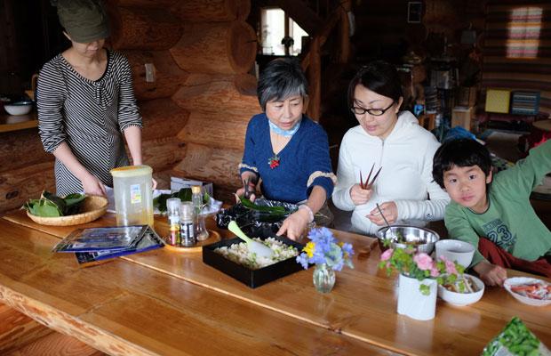子どもたちがつんできた笹の葉をお重にしきつめて、そこに酢飯を入れていく。中川さん(中央)の指示を聞きながら、友人ふたりがお寿司づくりにチャレンジ。