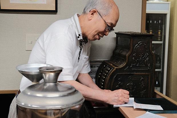 ご主人の三保谷卓(たかし)さんと、年代物のレジスター、大きな燗銅壺(かんどうこ)が、この店を象徴する3点セット。