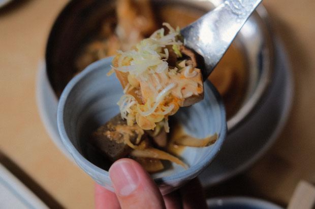 大衆居酒屋の定番メニュー、もつ煮込みは見た目も美しい。「きりりとした辛味噌風味で日本酒が進みます。鍋で熱々なのもうれしい。これも僕の定番です」(啓太さん)480円