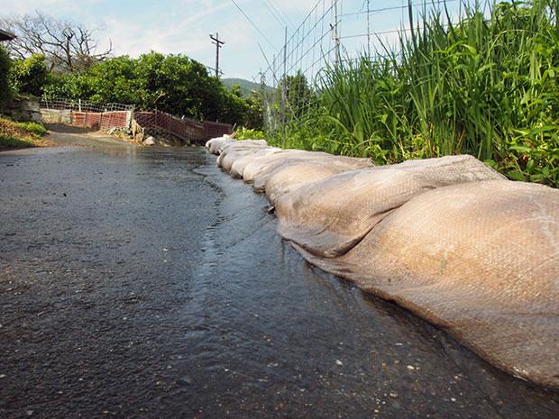 川からあふれた水が民家に流れ込んだため、土嚢で防ぐ。