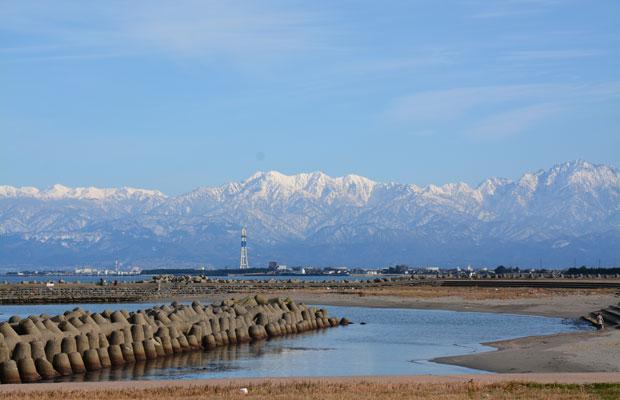 農村集落や地方都市の風景の背後に、CGでつくったかのような幻想的で雄大な山脈の姿が見えます。