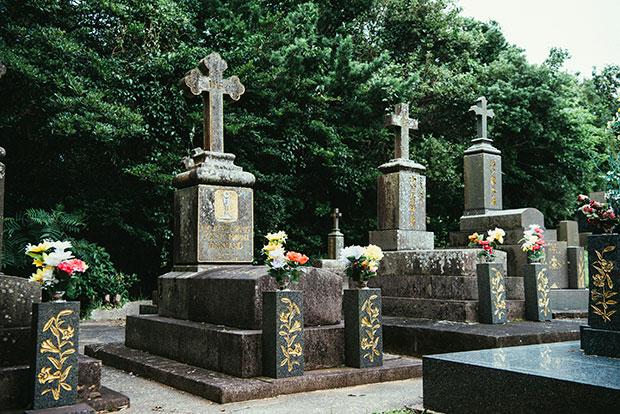 島内にあるカトリック共同墓地。島の御影石でつくられた十字架の墓石が整然と並びます。その中の一角にある、マルマン神父の墓(左)。当時の宣教師たちは、二度と祖国には帰れないかもしれないという覚悟で来日し、教えを広めました。キリスト教の布教だけでなく、西洋の学問や技術を伝えた功績も多大なものでした。