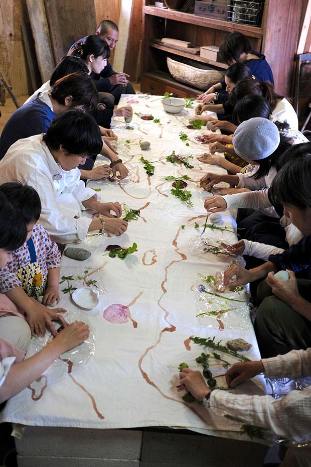 植物を直接布に貼り付けて石で叩くと、植物に含まれる色素によって布が染まる。