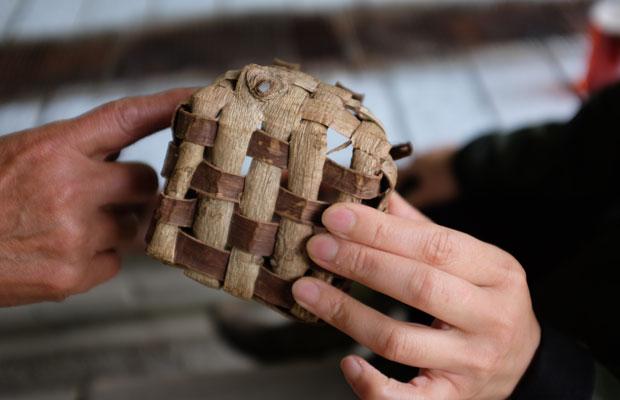 クルミの樹皮を短冊状に割いて編んだカゴ。樹皮の内側は最初は白いが、時間が経つと茶色く変色する。裏と表で色が異なるので、それを生かした編み目をつくることができる。