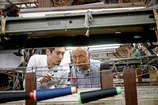 山田さんと生地を見ながら親密に話す〈葛利毛織工業〉の葛谷幸男社長。