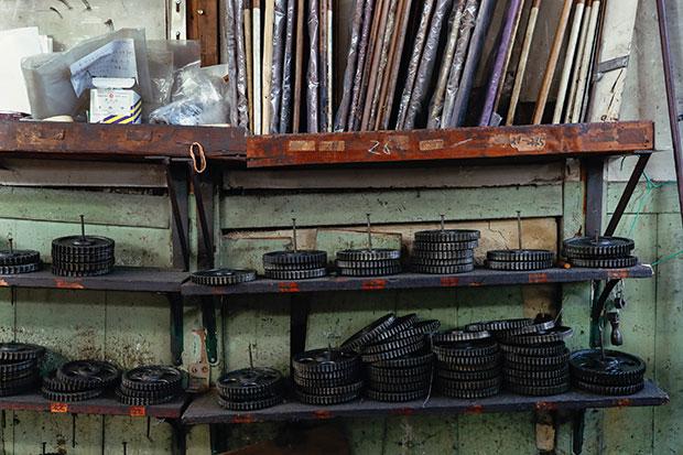 ションへル織機はかなりアナログな機械。歯車を交換して生地の密度を調整している。