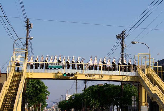 歩道橋に一列にならぶウマジンパレード参加者たち