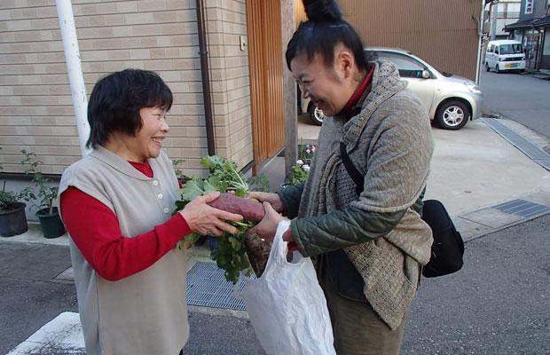 オープンから見守ってくれているお向かいのKさんから野菜をもらう妻。