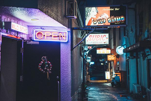 夕暮れと共に、少しずつ明かりが灯り始める外国人バー街。映画『坂道のアポロン』では、実際の外国人バー街に看板などのセットを追加し、佐世保在住の外国人エキストラの協力を得て、当時のジャズバーの通りの雰囲気を撮影したのだそう。