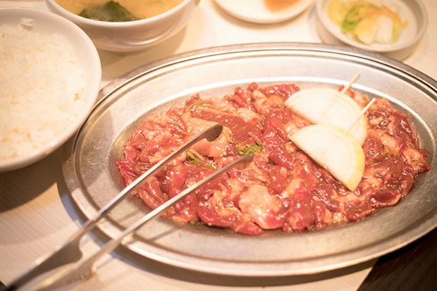 ジンギスカン定食(560円)は肉100グラムにライス、味噌汁、漬物、フルーツ付き。写真の肉は2人前。肉だけのオーダーだと350円。ライスは道産米の〈ふっくりんこ〉を使用。