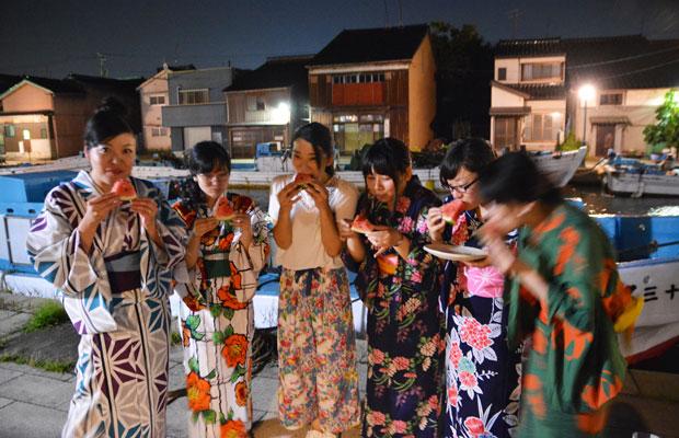 漁師町の川沿いにて、浴衣でスイカをほおばる女子たち。