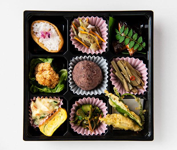 清庵弁当。右上から時計回りに、岩魚の甘露煮、ウドのきんぴら、葛の新芽・キクイモの葉・ミョウガの天ぷら、スベリヒユとキュウリの辛子和え、ポテトサラダとハコベの卵焼き、いわい鶏唐揚げ、葛花稲荷寿司、イタドリ・ミズの実・ウド・フキの酢の物、やまあいのぼたもち。