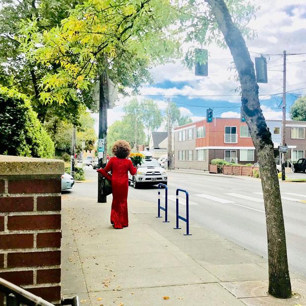 真っ赤なドレスで花束を抱えて歩く女性。映画のワンシーンのような情景が現実にある。(撮影:山中緑)