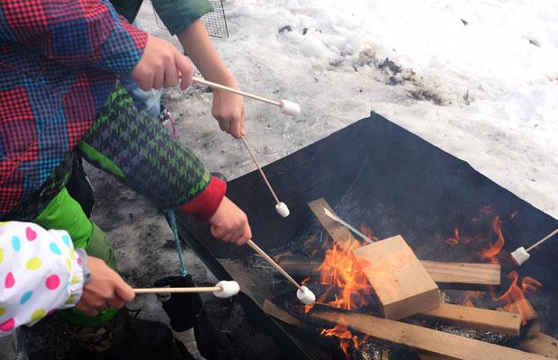 たき火でマシュマロを焼く子どもたち。