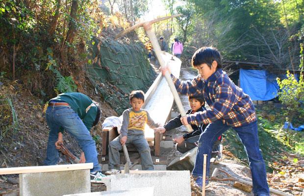 すべり台の制作の様子。異学年の子どもたちが協力して制作する。(写真提供:きのくに子どもの村学園)