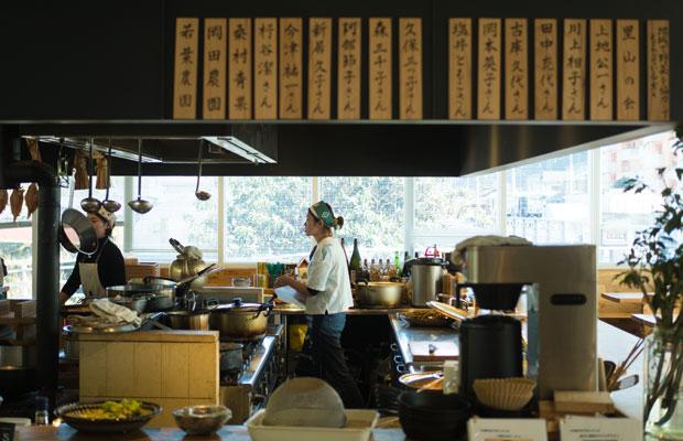 かま屋さんの台所で働く人たち。手前の壁には、生産者さんの名前札がずらり。