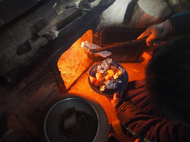床暖房オンドルの窯で栗きんとん用の芋を焼きます。黒豆は奥の鍋で煮ています。