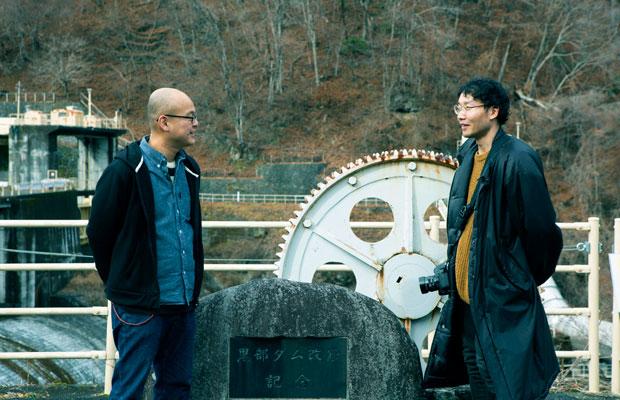 ダムのツアーのガイドを担当する地域おこし協力隊の石川充汰さんと。石川さんは写真を通して栗山の魅力発信もしている。