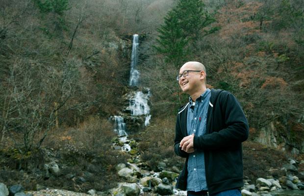 栗山の隠れた名所「蛇王の滝」を案内する疋野さん。地元の人には「そうめんの滝」と呼ばれていたそうで、なぜ現在の名前になったのか、そのエピソードも興味深い。