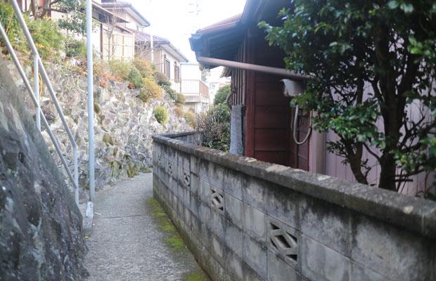 改修前の2号店前の様子。幅2メートルの狭い道を挟んだ向かい、ゴツゴツとした小松石の石垣が、1号店の敷地を支えている。