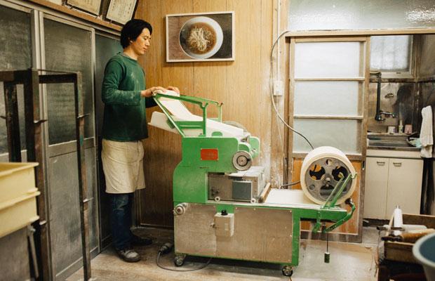 邦栄堂製麺の3代目・関 康さん。取材で訪れたときは、餃子の皮をつくっている最中だった。