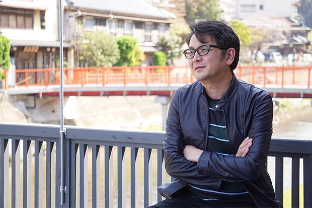 グラフィックデザイナー・白石慎一さん。カフェのテラスで自身のUターンの経緯やプロジェクトへの思いをうかがった。