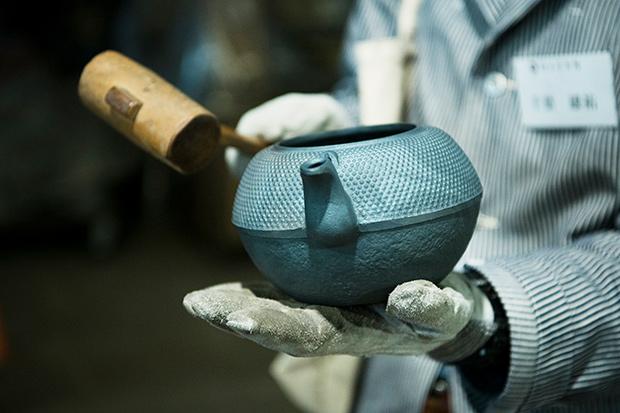鉄瓶を木づちで叩き、不良品がないか見極める作業を体験。
