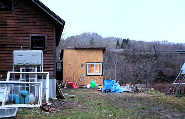 万字(まんじ)地区の岡林夫妻が住む家。母屋の隣にあるのが廃材を利用して建てた小屋。