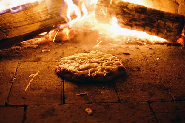 庭のピザ窯でピザを焼く。