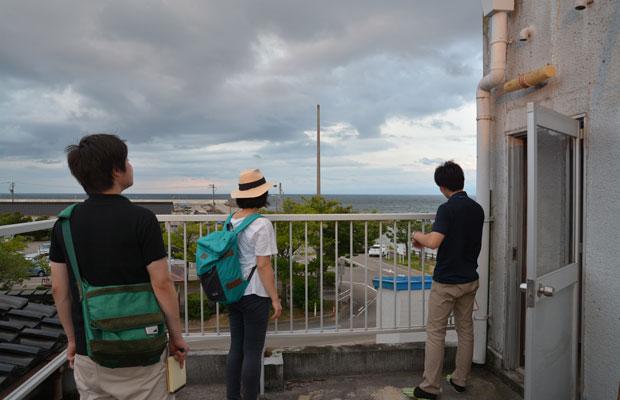 3階のベランダから海を眺める山本さんとツアー参加者。
