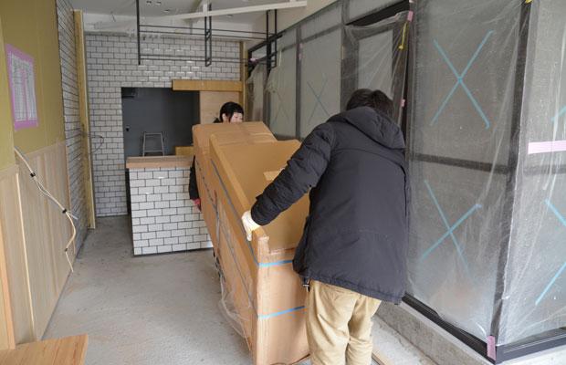 家庭用の流し台を運ぶふたり、厨房設備のコストダウン。