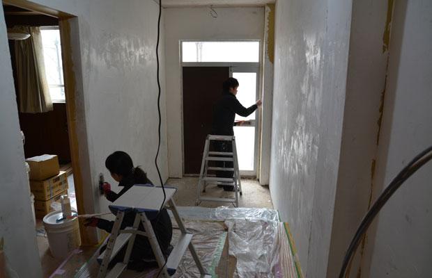 2階の玄関と通路の壁塗りをする山本さんご夫婦。