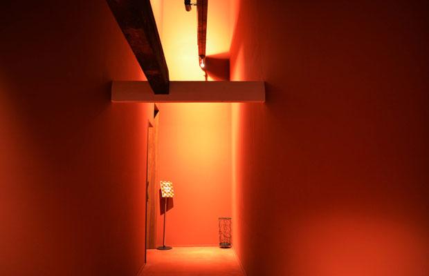 2階までの吹き抜けを、ベンガラ色の塗り壁にした贅沢な空間。