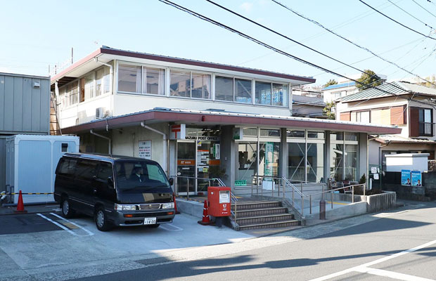 敷地内奥に新築の建物をつくるため、既存郵便局は解体されることに。2階には大きめのアルミサッシが整然と並んでいる。