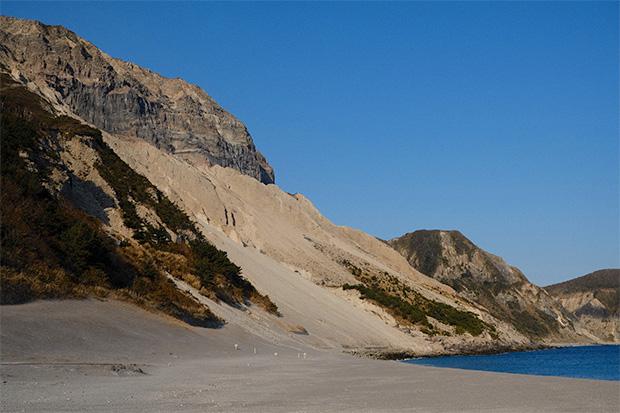 断崖と白砂のコントラストが美しい、多幸湾側から見る天上山。