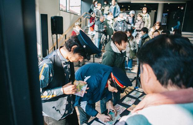 モノレールライブ、湘南江の島駅でのフリーライブを終え、2018年にリリースした6枚目のアルバム『鎌倉BEST』を購入した来場者にサインをするふたり。