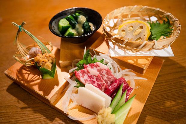 熊本に来たらまずは押さえておきたい郷土料理が一堂に盛られた〈郷土六花〉(990円)。右奥から時計回りに辛子蓮根、馬刺し三種(この日は霜降り、赤身、たてがみ)、山うに豆腐、一文字ぐるぐる。内容は贅沢でもお得な前菜。