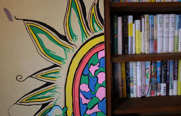 お店の壁に描かれたもうひとつの絵。ゆっくり過ごせるように本も置かれている。