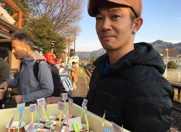 「資本ケーキ」を配る久永操さん。
