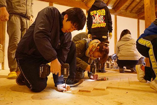 床板に細ビスを打ちこむ学生。