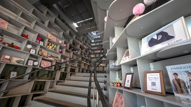 2階へとつながる階段〈おのたびゲート〉。尾道で生まれた作品や、近隣の商店街内のおすすめ店舗が紹介されている。photo by teruaki takekuni