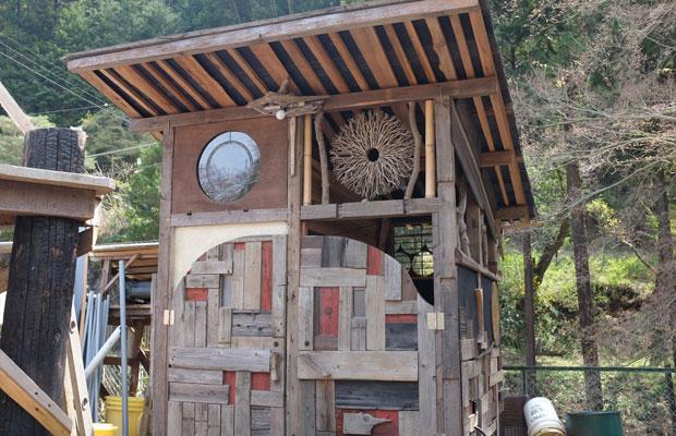 廃材でモザイクのようなドアをつくったコンポストトイレ小屋。