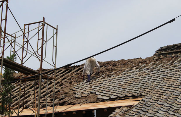 利活用が叶わなかった屋根瓦を落としていく工程。瓦の下には土と杉皮が葺かれている。