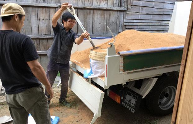 壁用の土(写真は中塗り用)をトラックで運び、土嚢袋に入れる作業。その後、網状の篩(ふるい)で粒の大きさを揃える作業も行います。