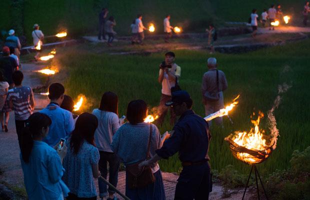 火手に火をつけてもらって田んぼのあぜ道を列になって歩いていきます。