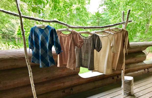 美流渡の森の山荘に飾られた〈うさと〉の服。布の素材は、コットン、ヘンプ、シルクの3種類。布はタイの農村に住む女性たちを中心に織られている。(写真提供:やまだひろこ)